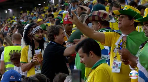 Narrador da Rádio Bandeirantes aparece na tela da TV Globo